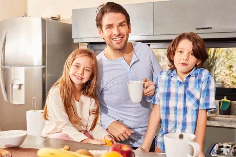 Padre y niños que desayunan en la cocina fotografía de archivo