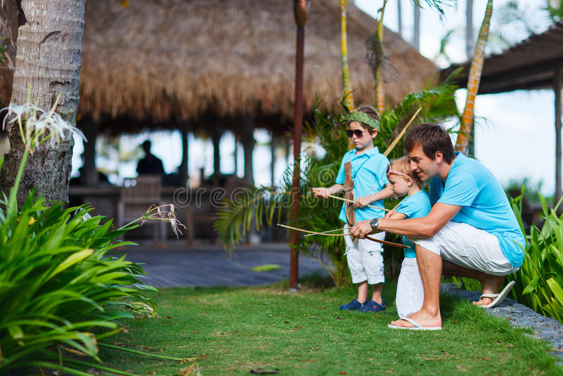 Padre y niños que juegan al aire libre imagenes de archivo