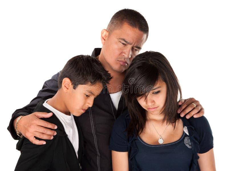 Padre y niños que parecen tristes fotografía de archivo
