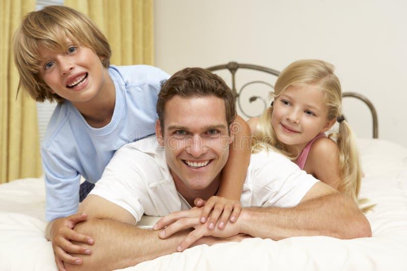 Padre y niños que se relajan en cama en el país foto de archivo libre de regalías