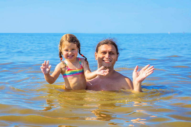 Padre y pequeña natación de la hija del bebé en el mar imagen de archivo