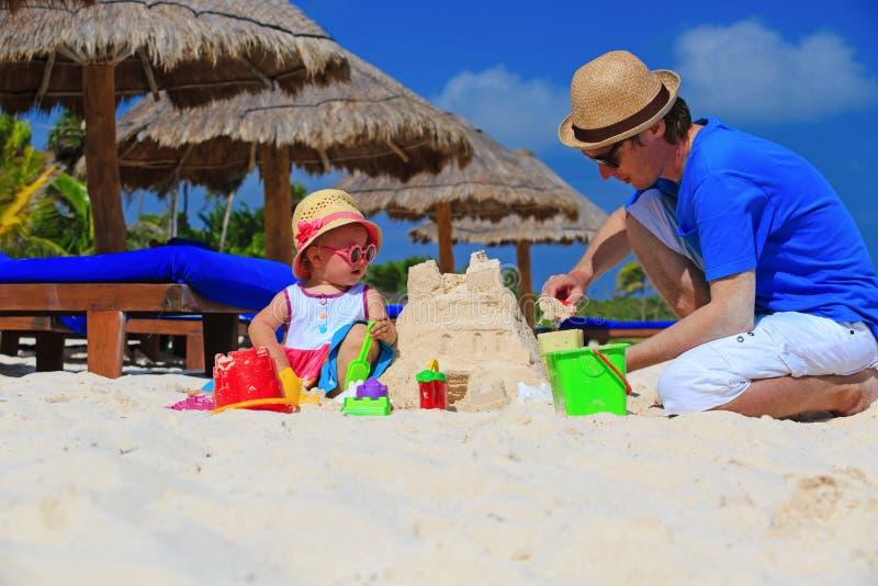Padre y pequeño castillo de arena del edificio de la hija encendido foto de archivo