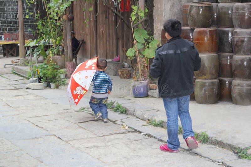 Padre y pequeño hijo en el pueblo antiguo Daxu, China fotografía de archivo