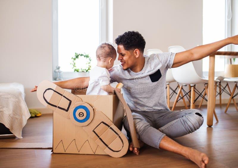 Padre y peque?o hijo del ni?o dentro en casa, jugando fotos de archivo libres de regalías