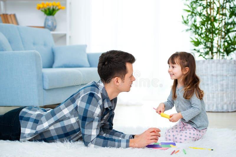 Padre y poca hija que tienen tiempo de la familia de la calidad junto en casa papá con la muchacha que miente en el dibujo calien imagen de archivo libre de regalías