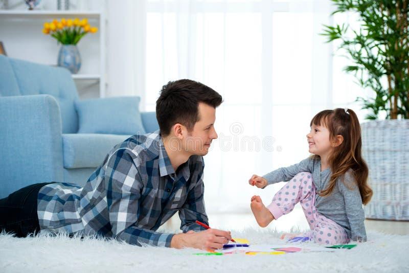 Padre y poca hija que tienen tiempo de la familia de la calidad junto en casa papá con la muchacha que miente en el dibujo calien fotos de archivo libres de regalías