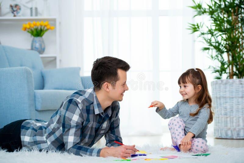 Padre y poca hija que tienen tiempo de la familia de la calidad junto en casa papá con la muchacha que miente en el dibujo calien imagenes de archivo
