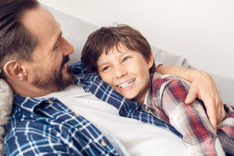 Padre y poco hijo en casa que mienten en el papá del sofá que abraza al muchacho que sonríe mirando a un lado el primer dreamful fotos de archivo libres de regalías