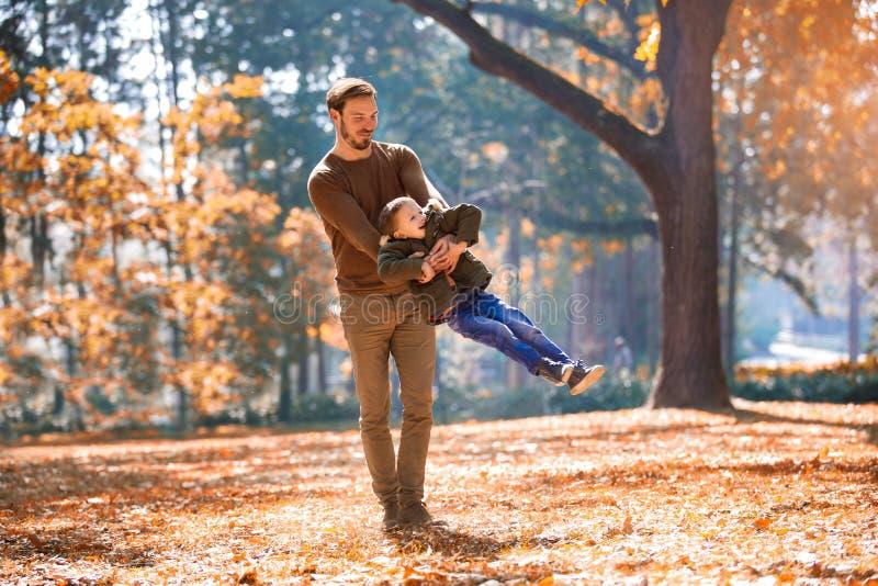 Padre y poco hijo que juegan y que tienen aire libre de la diversión sobre fondo del parque del otoño fotografía de archivo