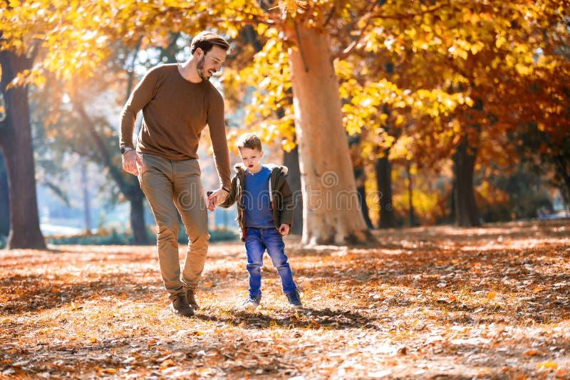 Padre y poco hijo que juegan y que tienen aire libre de la diversión sobre fondo del parque del otoño imagen de archivo
