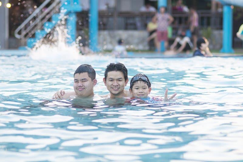 Padre y su juego de dos hijos en agua clara fotografía de archivo libre de regalías