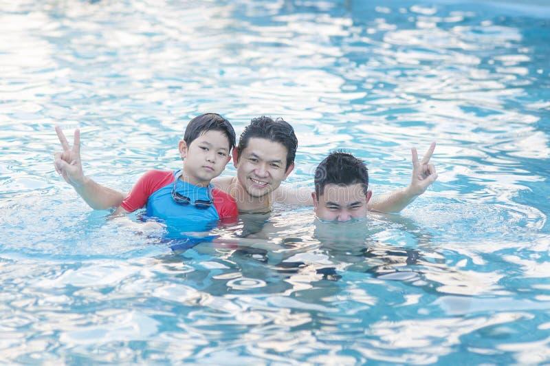 Padre y su juego de dos hijos en agua clara fotografía de archivo