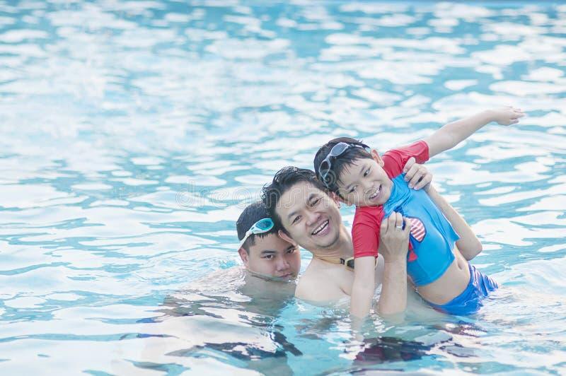 Padre y su juego de dos hijos en el agua fotos de archivo