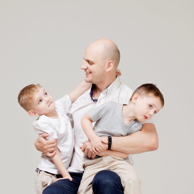 Padre y sus dos hijos, el hombre joven que cría a los niños, el retrato del concepto imagen de archivo libre de regalías