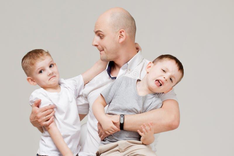 Padre y sus dos hijos, el hombre joven que cría a niños foto de archivo