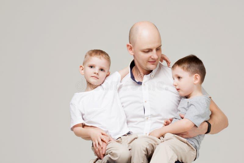 Padre y sus dos hijos, el hombre joven que cría a niños fotografía de archivo