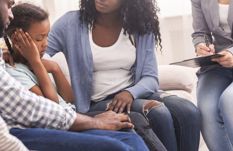 Padres africanos calmando a su pequeña y triste hija en consulta psicóloga imagen de archivo libre de regalías