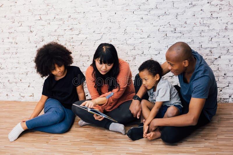 Padres afroamericanos que leen una historia de la fábula del cuento de hadas para los padres americanos kiAfrican que leen una hi foto de archivo