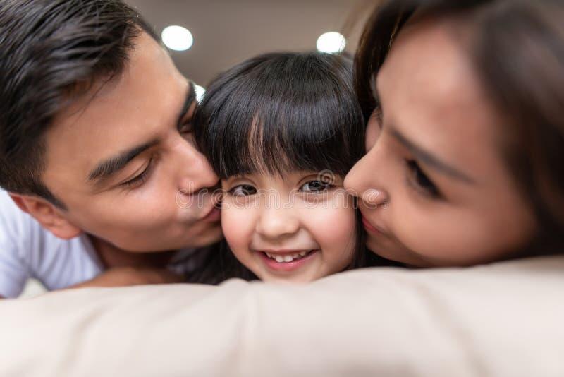 Padres asiáticos que besan a su poca hija en ambas mejillas fotos de archivo