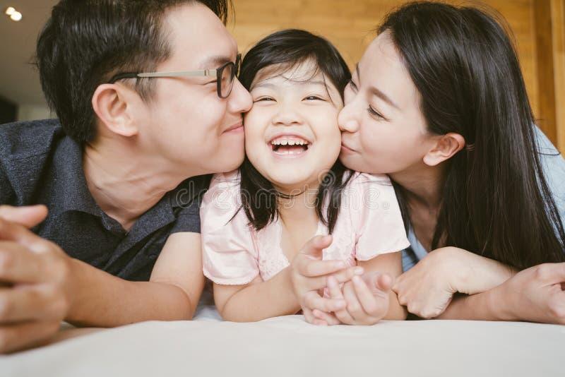 Padres asi?ticos que besan a su poca hija en ambas mejillas Retrato de la familia fotos de archivo libres de regalías