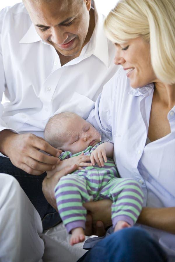 Padres cariñosos que sostienen dormido sano del bebé en brazos fotos de archivo libres de regalías