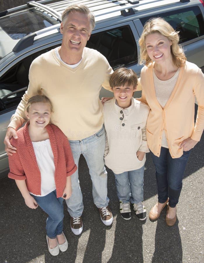 Padres cariñosos y niños que se oponen al coche foto de archivo
