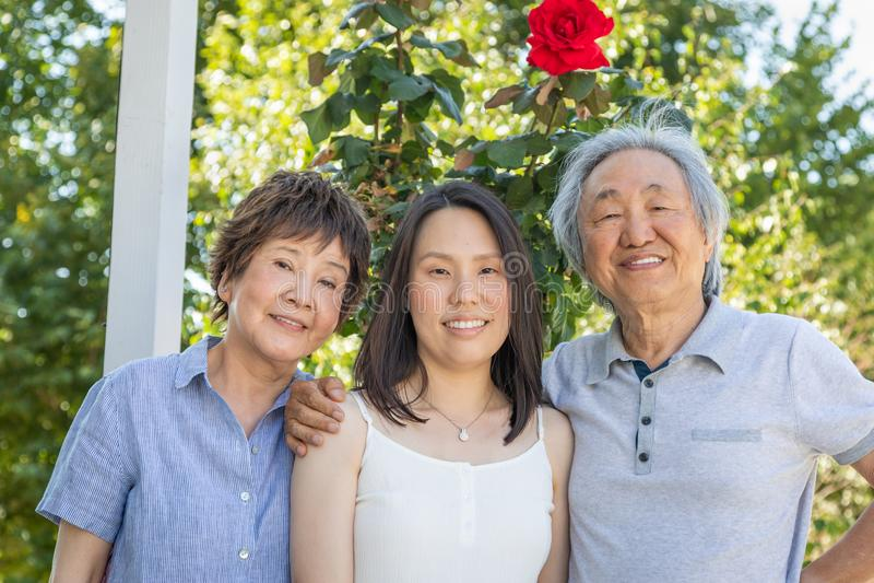 Padres chinos mayores e hija adulta joven al aire libre imagen de archivo