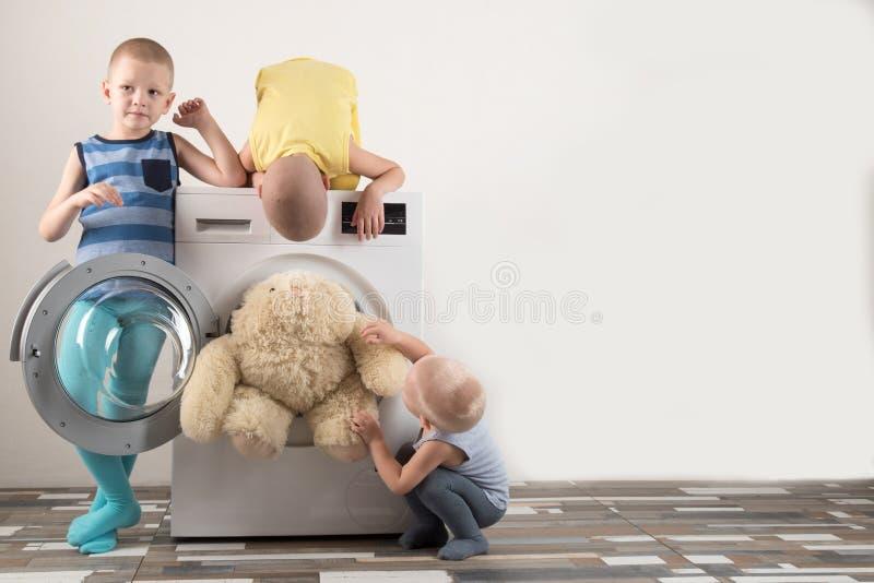 Padres comprados una nueva lavadora Los niños intentan girarlo y lavar los juguetes suaves Los muchachos felices están jugando en fotos de archivo
