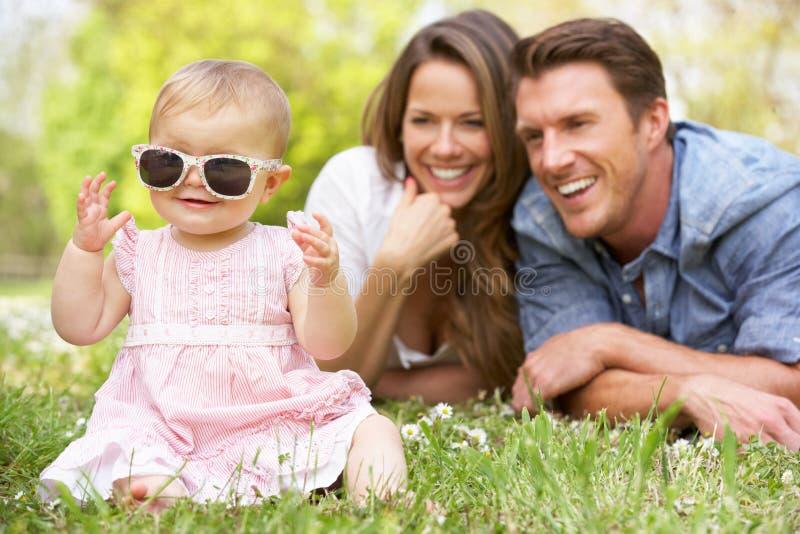 Padres con el bebé que se sienta en campo imagen de archivo