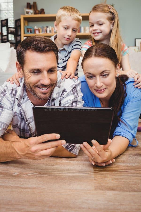 Padres con la tableta digital mientras que niños que se sientan en su parte posterior imagen de archivo libre de regalías