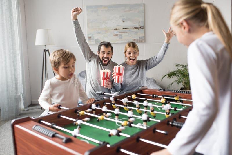 padres con los hermanos de observación de la palomitas de maíz que juegan a fútbol de la tabla imagen de archivo