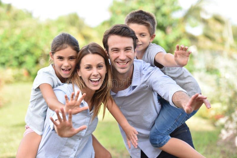 Padres con los niños que agitan las manos al aire libre imagen de archivo libre de regalías