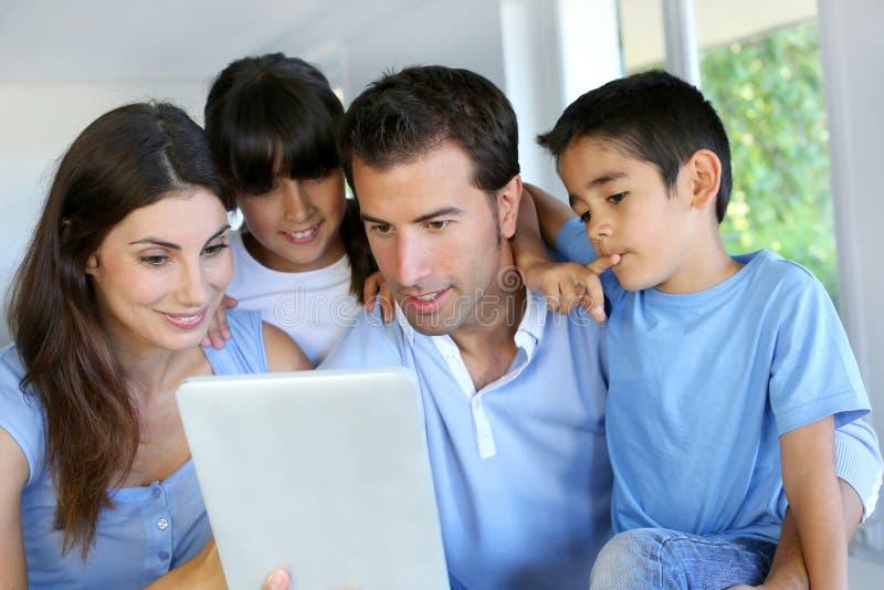 Padres con los niños que usan la tableta fotografía de archivo