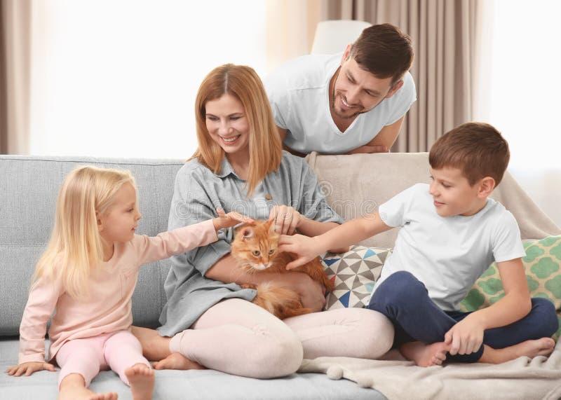 Padres con los niños y el gato foto de archivo