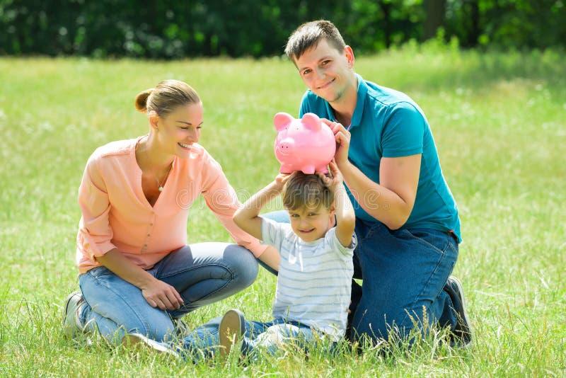 Padres con su hijo que sostiene la hucha imagenes de archivo