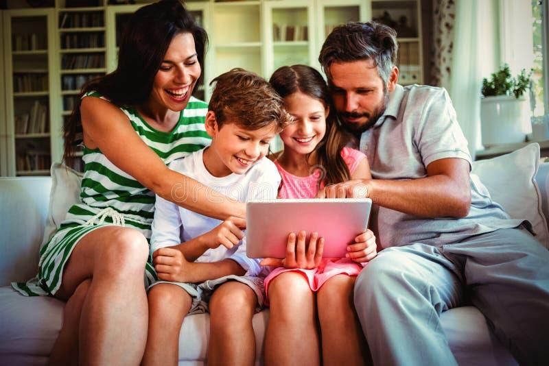 Padres con sus niños que se sientan en el sofá y que usan la tableta digital foto de archivo