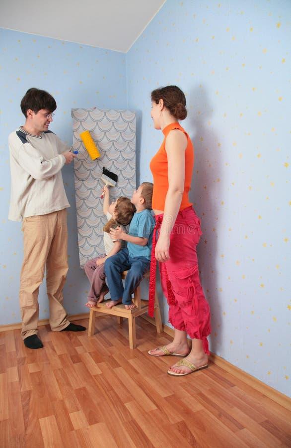 Padres de la ayuda de los niños para pegar los papeles pintados foto de archivo