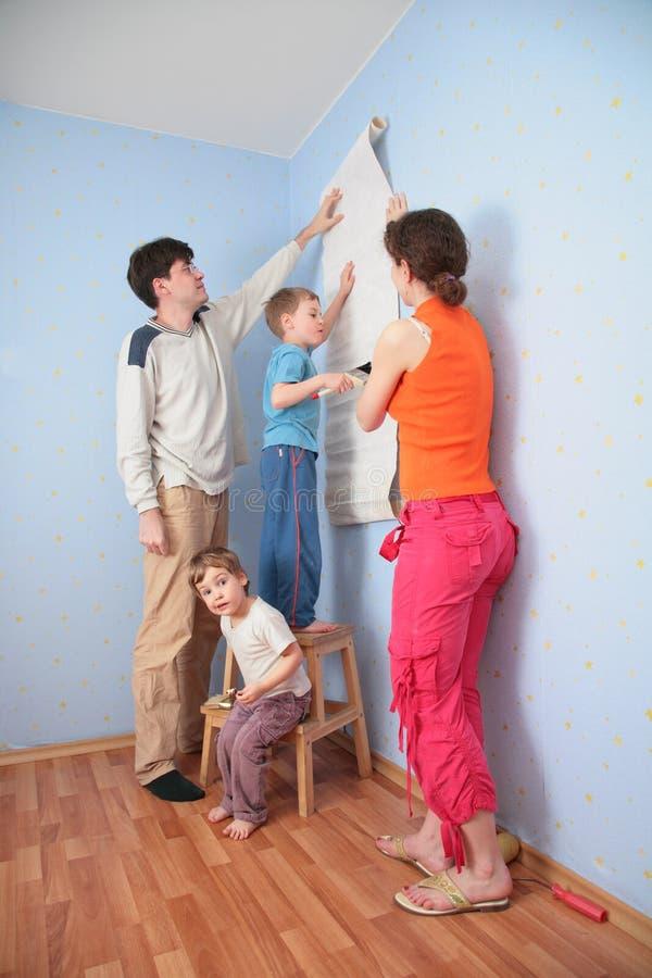 Padres de la ayuda del hijo para pegar los papeles pintados foto de archivo