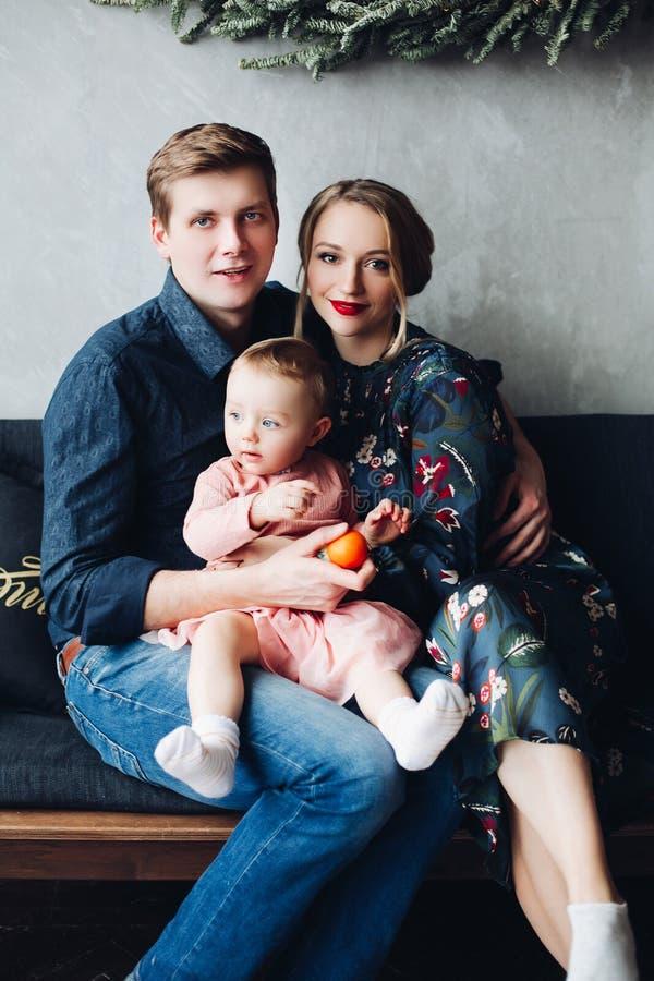 Padres e hija que se sientan en el sofá debajo de la guirnalda grande del abeto fotografía de archivo libre de regalías