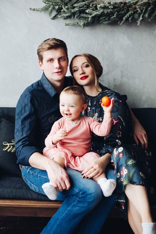 Padres e hija que se sientan en el sofá debajo de la guirnalda grande del abeto imágenes de archivo libres de regalías