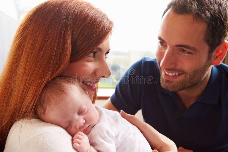 Padres en casa con la hija recién nacida durmiente del bebé imágenes de archivo libres de regalías
