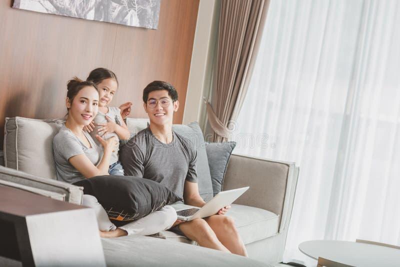 Padres felices con la hija que usa el ordenador portátil en sala de estar imagen de archivo