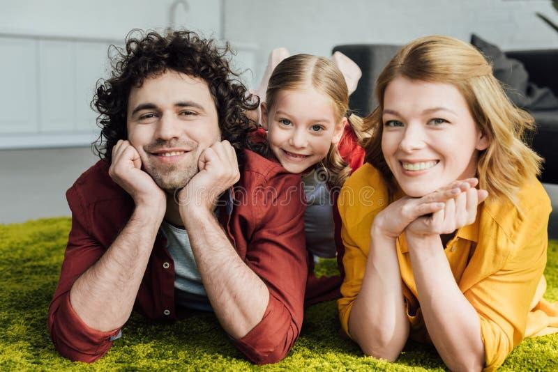 padres felices con la pequeña hija adorable que miente junto y que sonríe fotografía de archivo libre de regalías