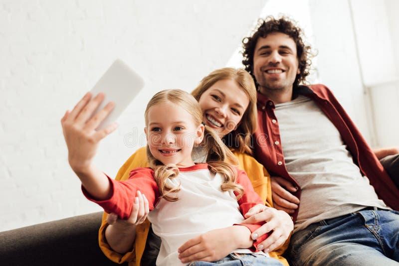padres felices con la pequeña hija adorable que toma el selfie foto de archivo