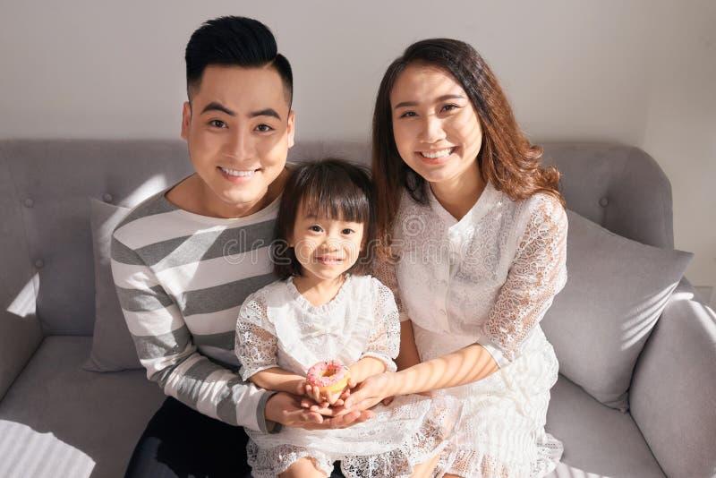Padres felices con la pequeña hija linda que se sienta en el sofá y el SMI fotografía de archivo