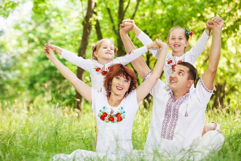 Padres felices con las pequeñas hijas en prado verde imagen de archivo libre de regalías