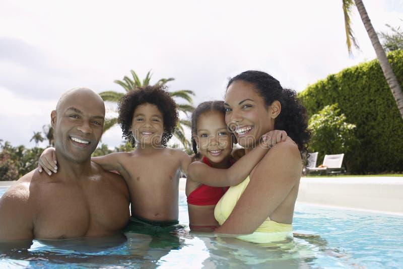 Padres felices con los niños en piscina imagen de archivo libre de regalías