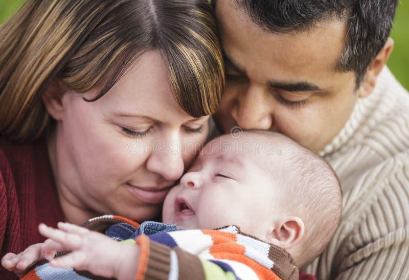 Padres felices de la raza mezclada que abrazan a su hijo imagenes de archivo
