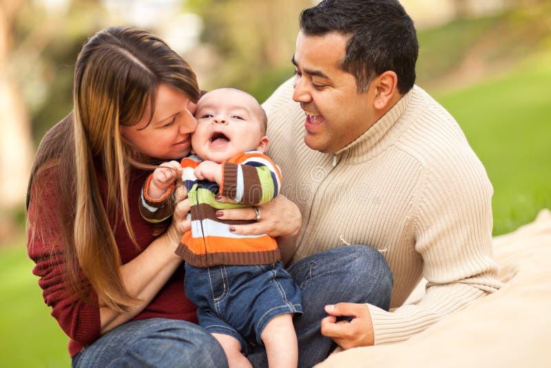 Padres felices de la raza mezclada que juegan con su hijo imagenes de archivo
