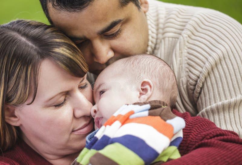 Padres felices de la raza mixta que abrazan a su hijo fotos de archivo libres de regalías